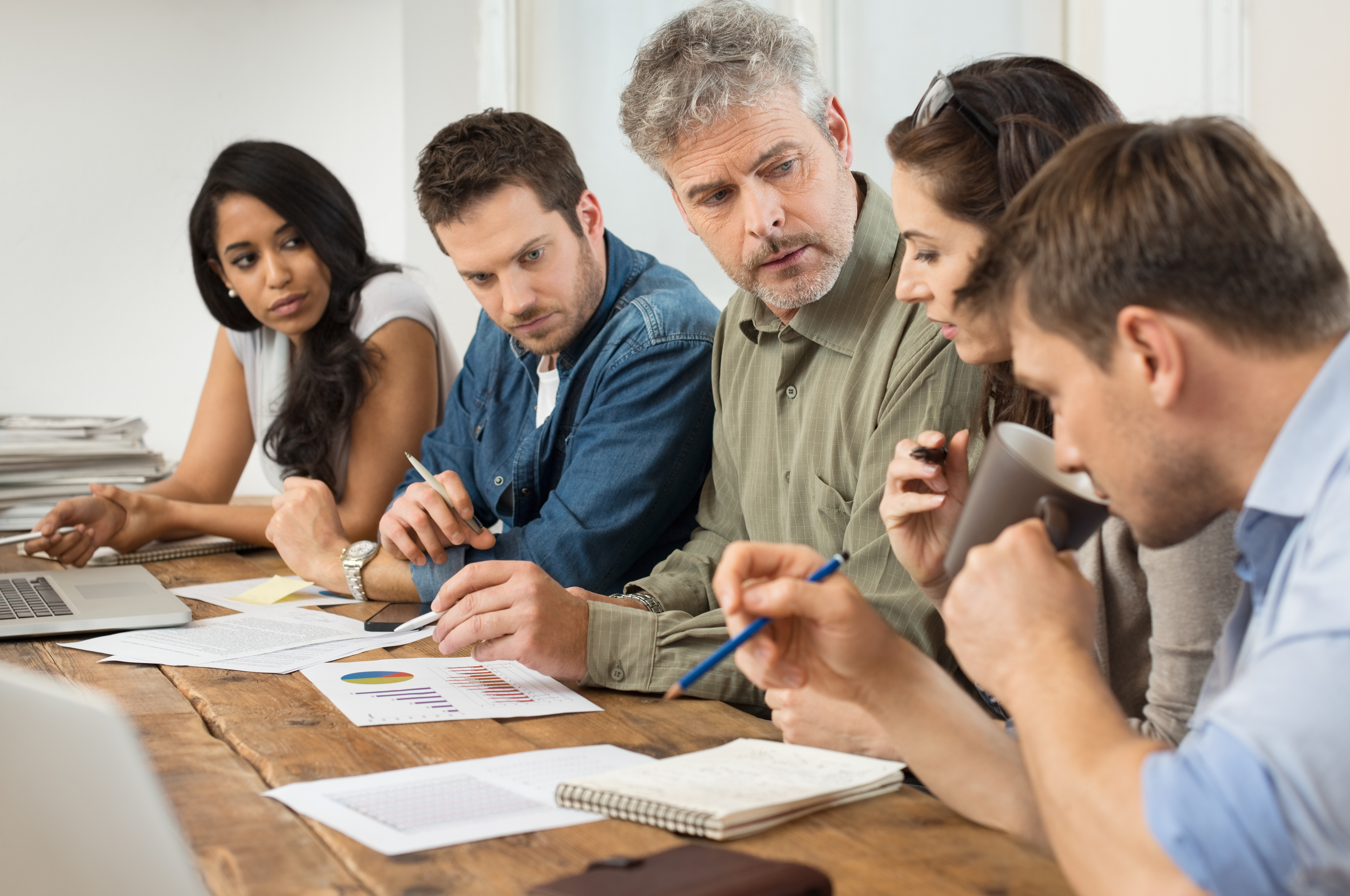office meeting. Businessman And Woman Discussing On Stockmarket Documents In Office. Team Of Business People Working Together Paperwork. Office Meeting Businesspeople